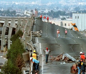 In this Oct. 19, 1989 file photo, workers check the damage to Interstate 880 in Oakland, Calif., after it collapsed during the Loma Prieta earthquake two days earlier. (AP Photo/Paul Sakuma)