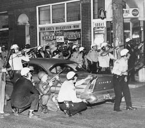 Cleveland police and newsmen take cover in the Hungarian neighborhood of Cleveland, OH, where a sniper was suspected of shooting from the roof tops on July 23, 1966.