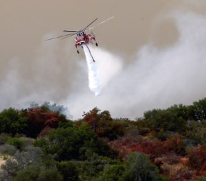 Helicopter drop of the Sherpa Fire in Santa Barbara County, Calif., Friday, June 17, 2016. An appeals court ruling means CAL FIRE can proceed with its suit against Presbyterian Camp and Conference Centers for the costs of fighting the massive wildfire that burned 7,500 acres. (AP Photo/Nick Ut)