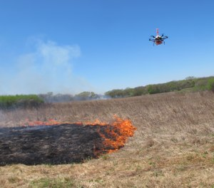 A drone designed to ignite controlled grass fires comes in for a landing in a field at the Homestead Monument of America in Beatrice, Neb., on Friday, April 22, 2016. (AP Photo/Grant Schulte)