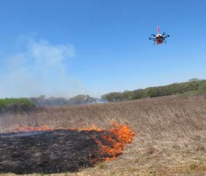 A drone designed to ignite controlled grass fires comes in for a landing in a field.