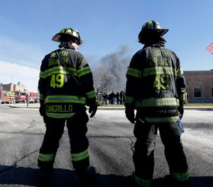 Firefighters waiting to load load their truck with water look on as a news conference is held in front of smoke rising at the site of a large warehouse fire a day after flames engulfed the facility, Friday, Feb. 12, 2016, in Hillsborough, N.J. (AP Photo/Julio Cortez)