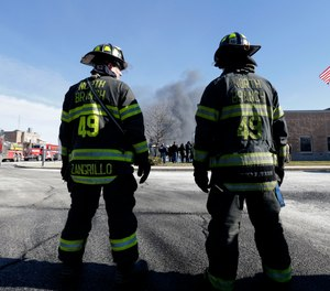 Firefighters waiting to load load their truck with water look on as a news conference is held in front of smoke rising at the site of a large warehouse fire a day after flames engulfed the facility, Friday, Feb. 12, 2016, in Hillsborough, N.J.
