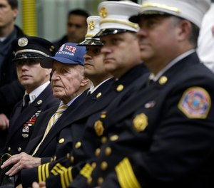 Retired Paterson firefighter Joe Parkin Sr., second left, 91, sits with others during ceremonies opening a new fire headquarters Monday, April 20, 2015, in Paterson, N.J. (AP Photo/Mel Evans)