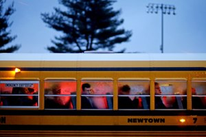 People arrive on a school bus at Newtown High School for a memorial vigil attended by President Barack Obama for the victims of the Sandy Hook Elementary School shooting in Newtown, Conn. (AP Photo/David Goldman, File)