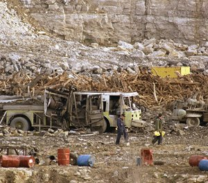 Investigators search through a highway construction site, Nov. 29, 1988 in Kansas City, Missouri where an explosion killed six firefighters. One of the five convicted in the deadly blast is requesting release, claiming her health problems put her at risk of becoming seriously ill or dying from COVID-19. (AP Photo/Sam Harrel)