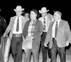 Convicted murderer Henry Lee Lucas is escorted by Louisiana and Texas police officers to a waiting car after arriving by plane in New Orleans, Jan. 8, 1985. Lucas was brought to the New Orleans area at the request of local police officials, hoping he will help solve as many as three dozen murder cases. (AP Photo/Bill Haber)