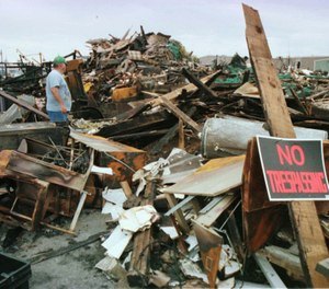 John Testaverde, plant manager of the Gloucester, Mass., Fisherman's Wharf looks over the charred remains of the wharf, Friday, Aug. 21, 1998, which was destroyed in a four-alarm fire. (Photo/AP, Lisa Poole)