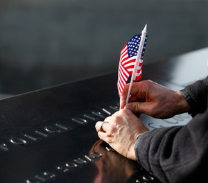 A man adjusts a flag that was inserted in the name of one of the New York City Police Department's first responders at the South Pool of the National September 11 Memorial & Museum, Monday, Nov. 9, 2015, in New York, following a ceremony honoring 9/11 first responders who were also military veterans. (AP Photo/Kathy Willens)