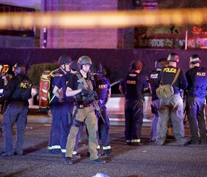 Police officers and medical personnel stand at the scene of a shooting near the Mandalay Bay resort and casino in Las Vegas.