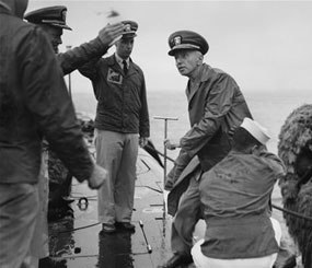 Rear Admiral Hyman G. Rickover, father of nuclear powered submarines, boards the USS Nautilus from the Navy Tug 534 in the Narrows below Brooklyn, New York on August 25, 1958. Cdr. William Anderson, head showing at left, awaits to greet the admiral aboard the U.S. Navy's first nuclear sub. Anderson is skipper of the Nautilus. Saluting at left center is Lt. Donald P. Hall, gunnery officer of the Nautilus. The craft returned earlier from four-month voyage.