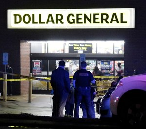 Law enforcement officers surround the Dollar General parking lot, located in the 1100 block of Opelika Road in Auburn, Ala, on Friday, Feb. 15, 2019. The site is the location of where an Auburn police officer was shot that afternoon after stopping a suspect vehicle in an attempted robbery case.