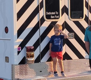 Ben Ford, 3, salutes the Emerson Ambulance Service from the tailboard of the rig dedicated to him.