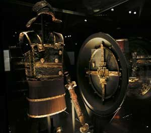The gold-decorated iron body armor, sword, and ceremonial shield of ancient Greek King Philip II of Macedon is displayed at Vergina museum, northern Greece. Modern body armor worn today by police is lighter and more comfortable, but serves precisely the same purpose as armor from ancient history.