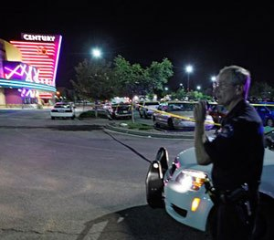 An Aurora police officer talks on his radio outside the Century 16 movie theatre in Aurora (Colo.) on July 20, 2012 during the chaotic response to the mass shooting there.