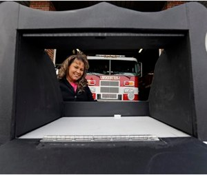Monica Kelsey, firefighter and medic who is president of Safe Haven Baby Boxes Inc., poses with a prototype of a baby box, where parents could surrender their newborns anonymously, outside her fire station in Woodburn, Ind.. (AP Photo/Michael Conroy)