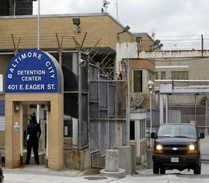 In this Thursday, June 6, 2013, file photo, a prisoner transport van departs from the Baltimore City Detention Center, in Baltimore where a contraband conspiracy revealed the widespread corruption inside the facility involving the Black Guerilla Family. (AP Image)