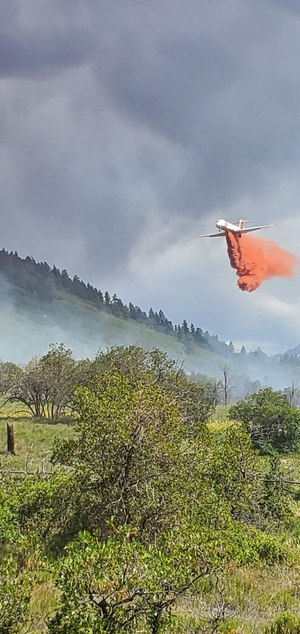 Everyone gets in the game on mutual aid. Here, an aerial super tanker deployed from Colorado Springs drops a load on the Green Meadows Fire in July 2020, when firefighters from Norwood, Telluride and other agencies joined forces in successful WUI home defense. Homes were saved with the help of a mutual mitigation program in collaboration with the West Region Wildfire Council.