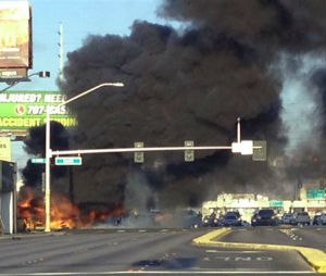 Smoke filled the sky after a fire tore through a minibus following a collision in Las Vegas on Saturday. (Associated Press)