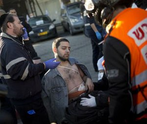 "An injured man is treated by paramedics at the scene of a stabbing in Tel Aviv, Israel, Wednesday, Jan. 21, 2015. A Palestinian man stabbed nine people, injuring several seriously, on a bus in central Tel Aviv before he was chased down, shot and arrested, Israeli police said Wednesday, describing the assault as a ""terror attack"" in the latest in a spate of violence, the worst Israel has seen in almost a decade. (AP Photo/Oded Balilty)"