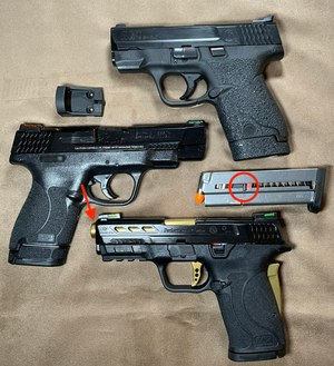 Top to bottom: Original Shield with Talon Grips, Performance Center Shield 2.0 and Performance Center Shield 2.0 EZ. The barrel port (arrow) is in front of the slide on the EZ which limits muzzle rise while keeping crud out of the slide. Also note the thumb stud (circled) used to retract the follower making mag loading drop-in simple.