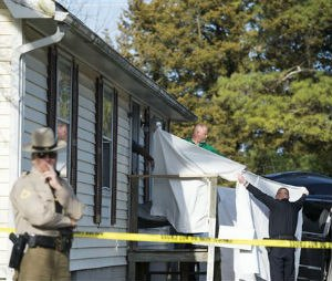 Sheets are held as a body is removed from a residence where police say seven children and one adult have been found dead Monday, April 6, 2015, in Princess Anne, Md. Officers were sent to the home Monday after being contacted by a concerned co-worker of the adult. (AP Photo/The Daily Times, Joe Lamberti)