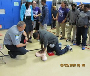 Dave Mitkowski watches as a student practices hands-only CPR. (Image Caesar Rondina)