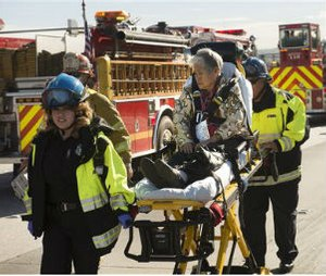 A woman is carried on a stretcher after a collision involving a commuter bus and two big rigs on eastbound State Route 60 at 7th Street in Hacienda Heights, Calif. on Wednesday, Jan. 7, 2015. (AP Photo/San Gabriel Valley Tribune, Keith Durflinger)