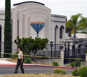A San Diego county sheriff's deputy stands in front of the Poway Chabad Synagogue in Poway, Calif.