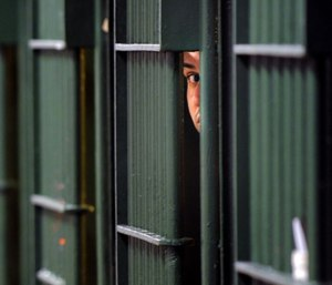 An inmate peaks through the bars at the restrictive housing unit, formerly known as solitary confinement, at the Men's Central Jail in Los Angeles. (Photo/Wally Skalij of Los Angeles Times via TNS)