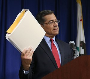 California Attorney General Xavier Becerra displays one of the three binders containing his office's investigation into last year's fatal shooting of Stephon Clark by two Sacramento Police Officers (AP Photo/Rich Pedroncelli)