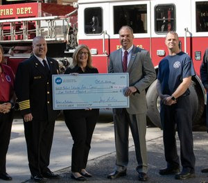 ADT's Jay Robertson, who is also a volunteer firefighter, presents a $100,000 contribution to Heather Schafer, CEO of the National Volunteer Fire Council, as part of ADT's commitment to help bring awareness to recruiting and retaining more volunteer firefighters in communities across America (Image courtesy of ADT)
