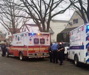 Emergency personnel gather near a home where police say four people were found dead in an apparent carbon monoxide poisoning in the Queens borough of New York on Friday, April 10, 2015. (AP Photo/Mike Balsamo)