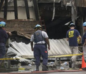 Federal investigators look over the scene after the Charleston fire.