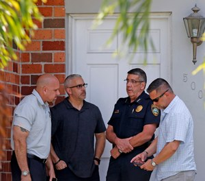 Surfside Chief of Police Julio Yero, second from right, speaks with investigators outside the home of Sol Pais, Wednesday, April 17, 2019, in Surfside, Fla. (Al Diaz/Miami Herald via AP)