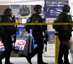 Heavily armed police officers exit the Costco following a shooting inside the wholesale warehouse in Corona, Calif. (Will Lester/Inland Valley Daily Bulletin/SCNG via AP)