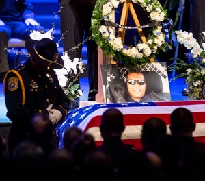 """a picture of slain Newman Police Cpl. Ronil """"Ron"""" Singh rests atop the casket during his funeral in Modesto, Calif. (AP Photo/Noah Berger, File)"""