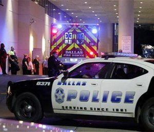 A Dallas police vehicle follows behind an ambulance carrying a patient to the emergency department at Baylor University Medical Center, as police and others stand near the emergency entrance early Friday, July 8, 2016, in Dallas. (AP Photo/Tony Gutierrez)