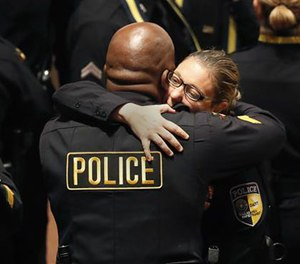 DART police officer Misty McBride, right, is embraced by a fellow officer as she arrives for a memorial at the Morton H. Meyerson Symphony Center, Tuesday, July 12, 2016, in Dallas. Five police officers were killed and several injured, including McBride, during a shooting in downtown Dallas last Thursday night.