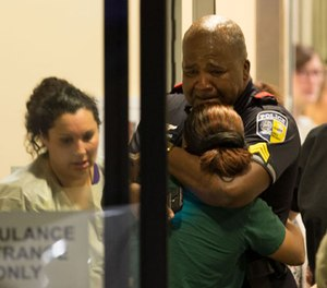 A Dallas Area Rapid Transit police officer receives comfort at the Baylor University Hospital emergency room entrance Thursday, July 7, 2016, in Dallas. (Ting Shen/The Dallas Morning News via AP)