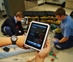 Close-up of watch and tablet screen during a simulation debriefing.