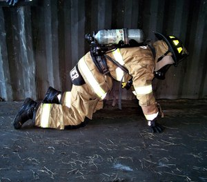 A firefighter uses a traditional search on hands and knees to search for the door. They are searching the wall for the door or following directives from the officer with the TIC to follow a wall until the open door is located.
