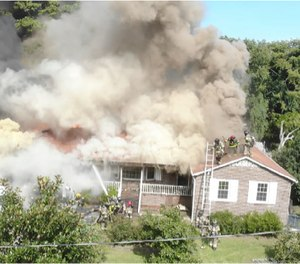 A drone films the exterior of a house fire, watching crews operating on roof.
