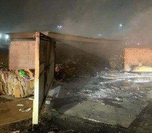 Modesto firefighters rescued a man locked inside a burning dumpster enclosure on Friday.