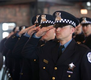 Police recruits salute during the playing of the National Anthem at the Chicago Police Department recruit graduation ceremony at Chicago's Navy Pier Grand Ballroom March 30. Four Illinois National Guard Soldiers were among the 107 recruits that graduated, dedicating themselves to serving the community and the city of Chicago.