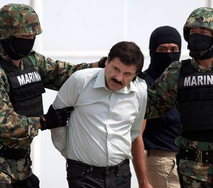 "Joaquin ""El Chapo"" Guzman, center, is escorted to a helicopter in handcuffs by Mexican navy marines at a hanger in Mexico City, after he was captured overnight in the beach resort town of Mazatlan.  (AP Photo/Eduardo Verdugo, File)"