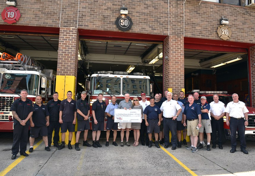 Members of Engine 50/Ladder 19 present a donation check to Building Homes for Heroes.