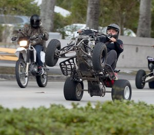 An ATV rider does a wheelie while riding in Miami Lakes on Monday, Jan. 21, 2019. The group caught the attention of BSO near Hallandale Beach Blvd. and Federal Hwy., but moved southwest, joining others and dipping into Miami Dade County. In recent years, ATVs and motorcycles have swarmed the streets in support of the 'Wheels Up, Guns Down' movement. (Amy Beth Bennett/South Florida Sun Sentinel/TNS)