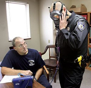 Alton, Ill., Fire Department engineer Bob Eichen, left, uses a machine to run a series of five tests on the gas mask of Alton Police officer Michael Beaber, right, at the Don Twichell Memorial Fire Station in Alton. (AP Photo/The Telegraph, John Badman)