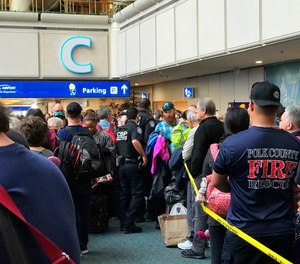 People wait to get through security at the Orlando International Airport following a security incident on Saturday, Feb. 2, 2019. Passengers on shuttles to gates at Florida's busiest airport had to be brought back for a second screening, bringing security checkpoints to a temporary standstill. A spokeswoman for Orlando International Airport told television station WKMG on Saturday that the passengers were returned in